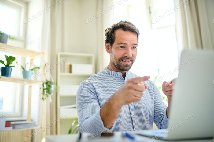 Mature businessman having video call on laptop at home