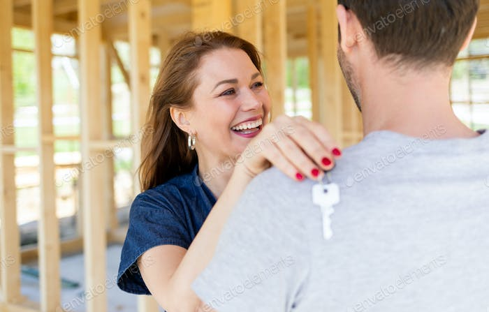 Wife holding keys hugging husband inside of their new home under construction, dreams come true
