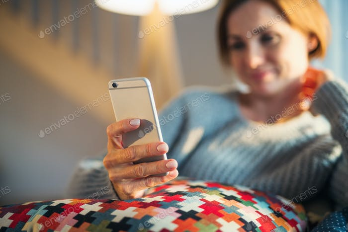 A young woman sitting indoors on a sofa at home, using smartphone.