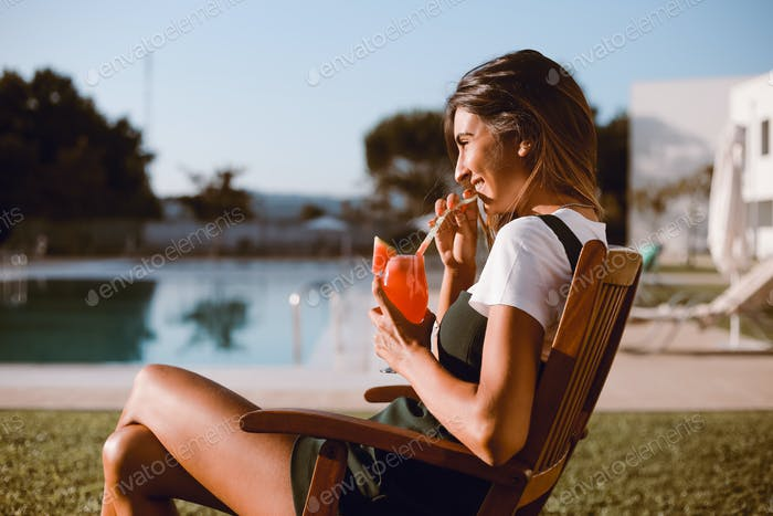 Hermosa mujer bebiendo cóctel cerca de la piscina