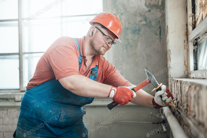 Builder in th uniform at a construction site working on a brick wall with a hammer