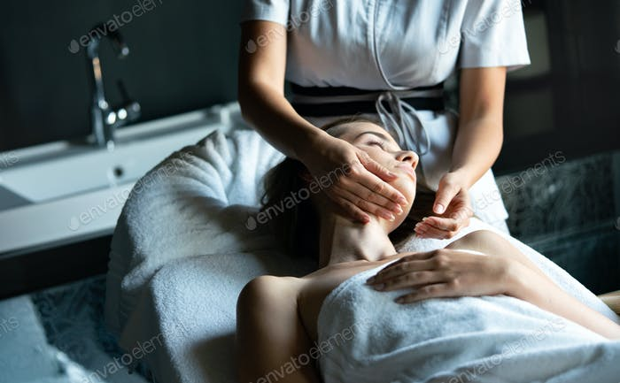 Young beautiful female in beauty salon getting spa massage