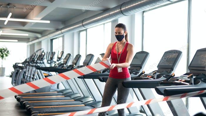 Mujer con máscara facial marcando distancia segura en el gimnasio, concepto coronavirus