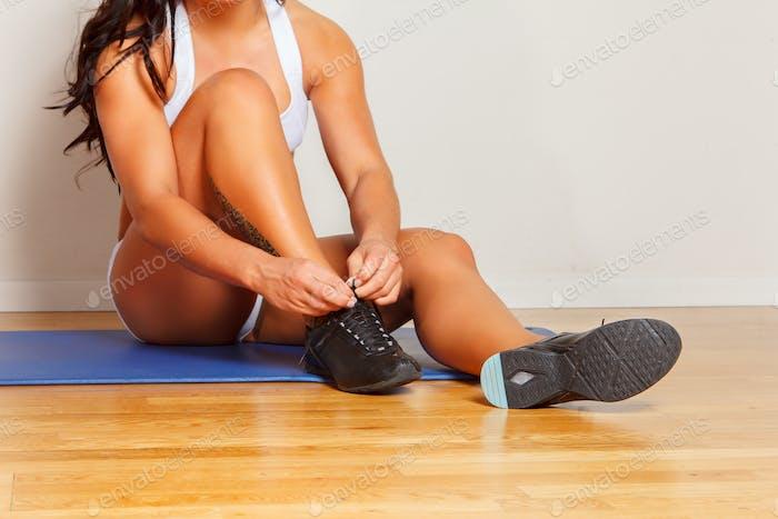 Woman's legs on blue fitness mat.