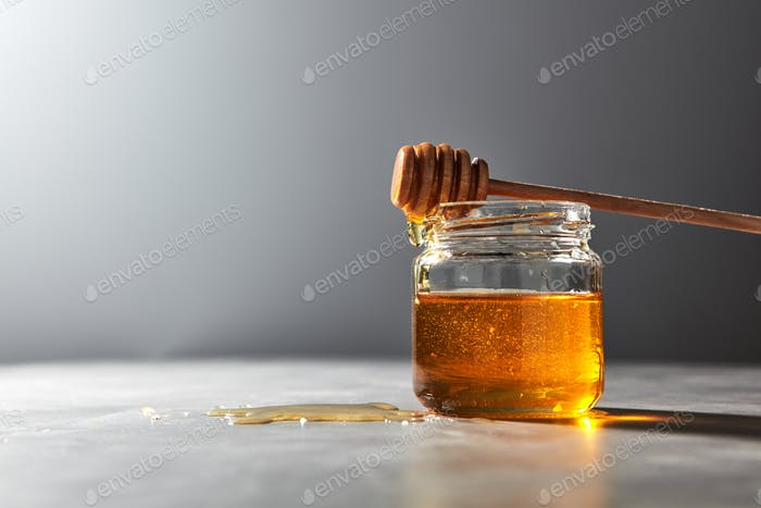 Wooden honey spoon above on a glass jar full natural organic syrup in a glass pot on a gray stone