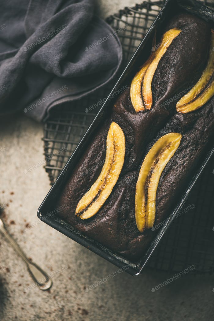 Chocolate banana cake with cinnamon in baking tin, vertical composition