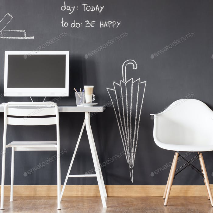 Habitación con pared de pizarra y escritorio