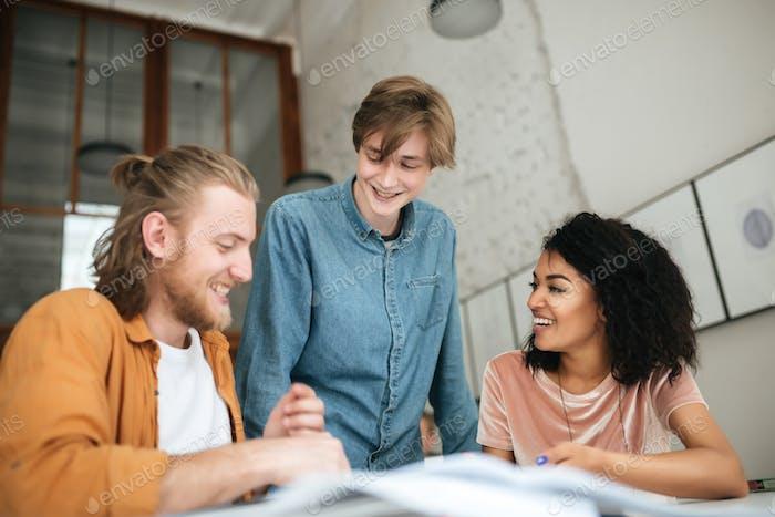 Junge fröhliche Leute diskutieren etwas im Büro.
