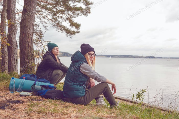 Young traveler women resting during traveling near the lake