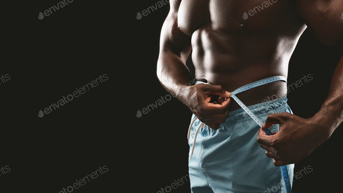Muscular black man measuring his waist with measure tape