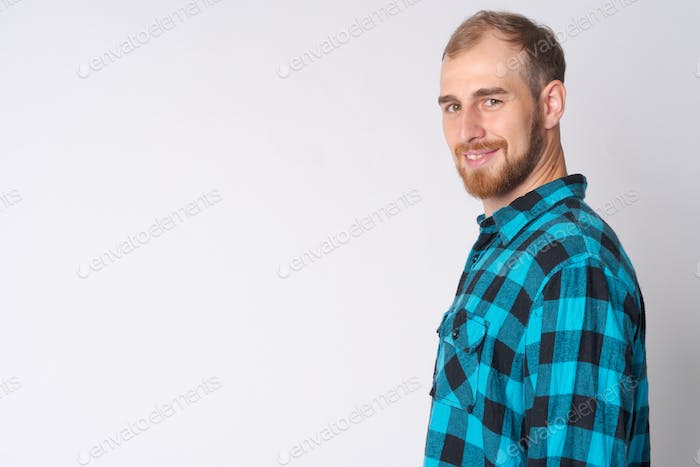 Profile view of happy young bearded hipster man looking at camera