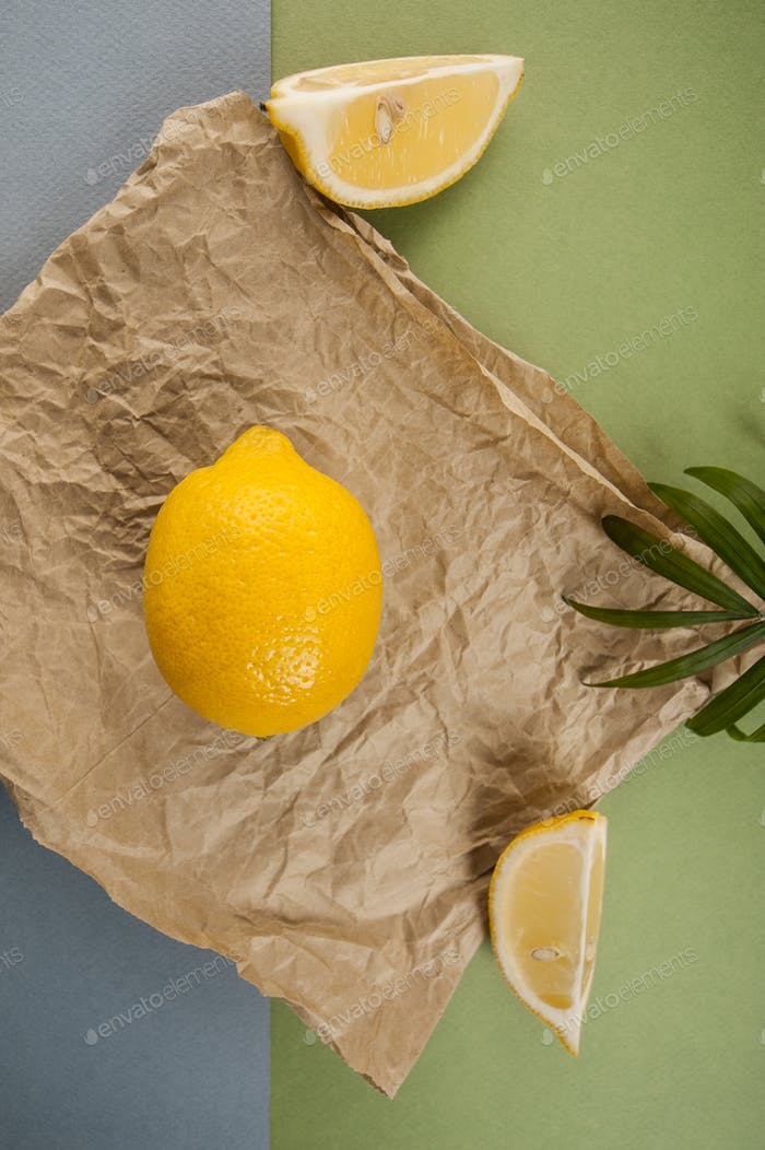 Minimalistic composition with a ripe lemon on kraft paper on a b