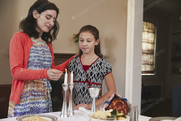 Jewish mother and daughter lighting candles for Shabbat meal