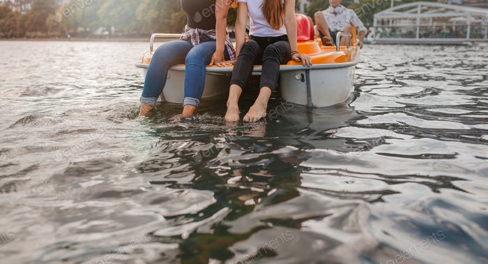 Two young women on a pedalo boat with feet in water