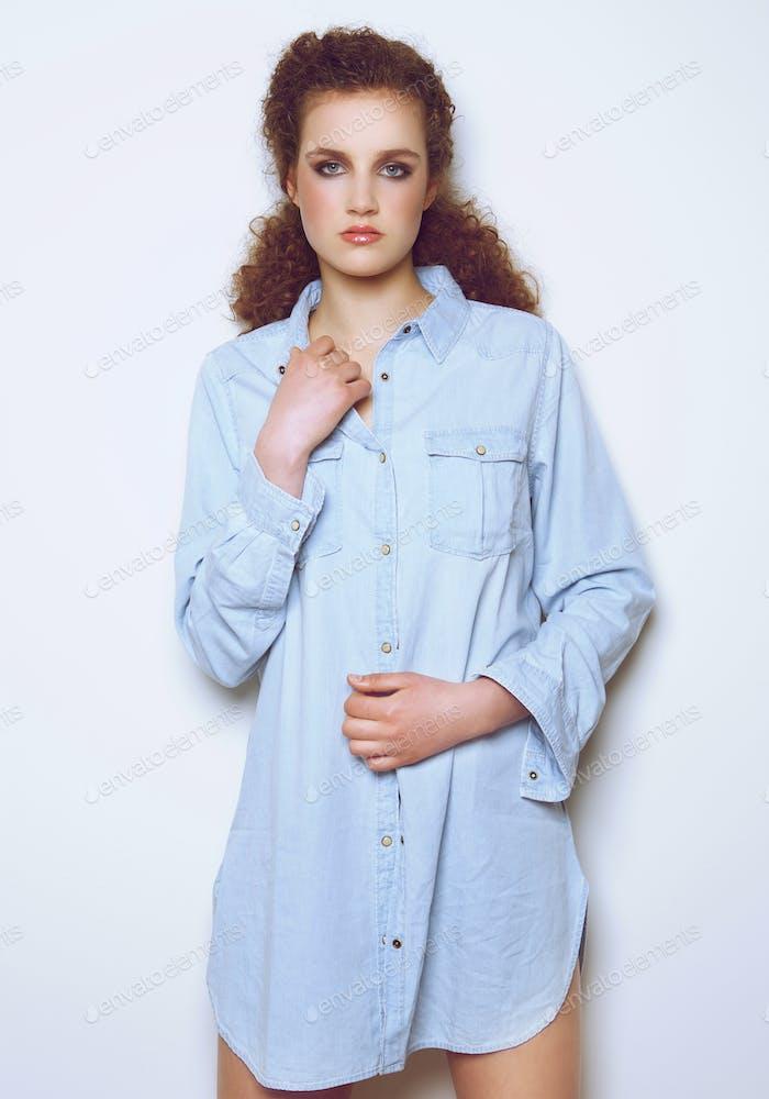 Elegant female fashion model posing in denim shirt