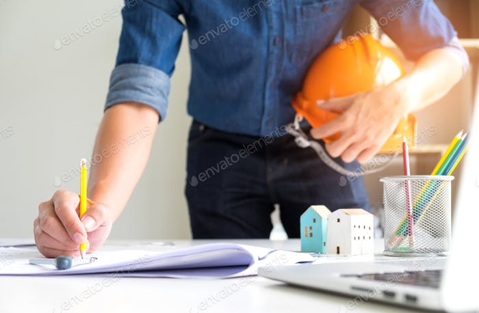 Architects are using drawing pencils,On the other hand holds a safety hat.