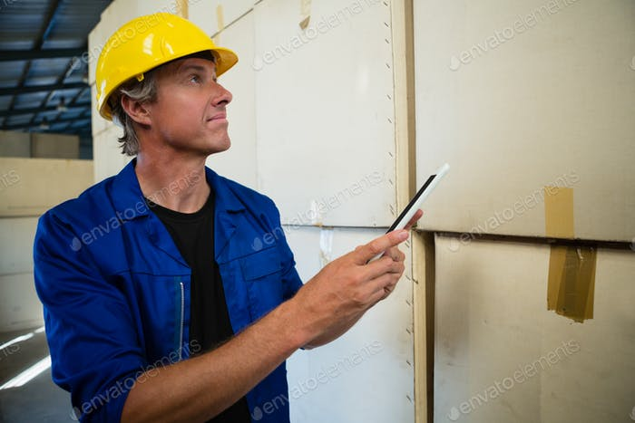 Worker maintaining record on digital tablet