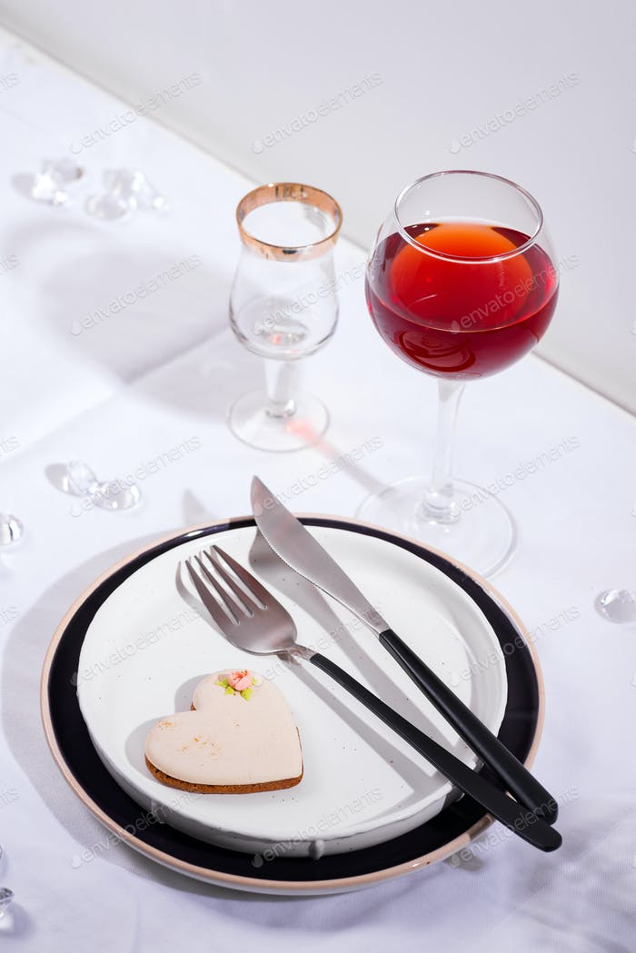 Tableware and decorations for serving a festive table. Plates, red wine glass and cutlery with heart