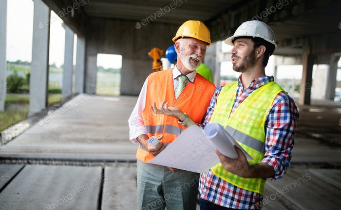 Confident team of architects and engineers working together on construction site