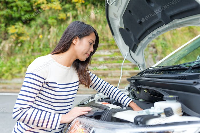 Woman trying to repair a car engine