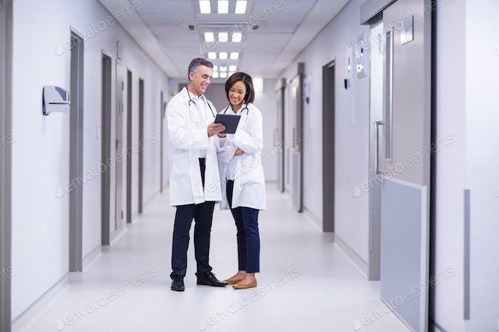 Ärzte mit digitalem Tablet im Korridor