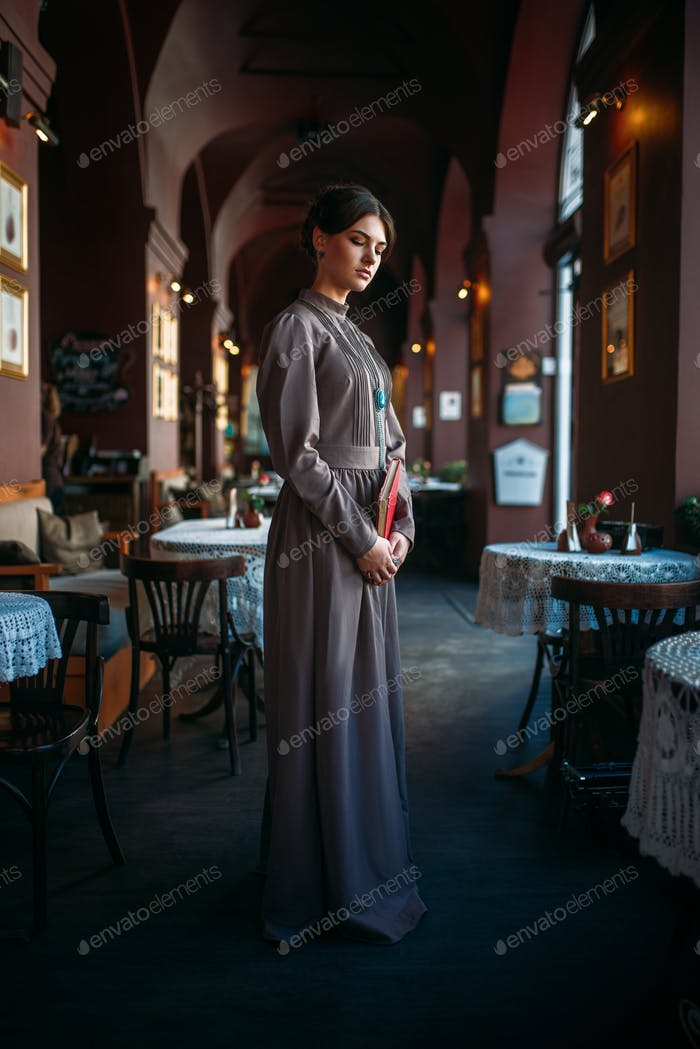 Young female person stands inside of cafe