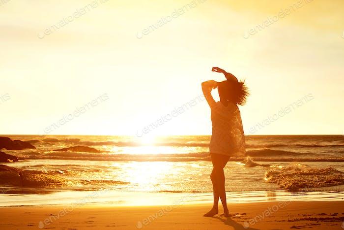 Silueta Mujer joven caminando en Playa durante la puesta del sol