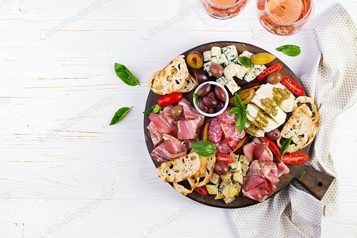 Antipasto platter with ham, prosciutto, salami, blue cheese, mozzarella with pesto