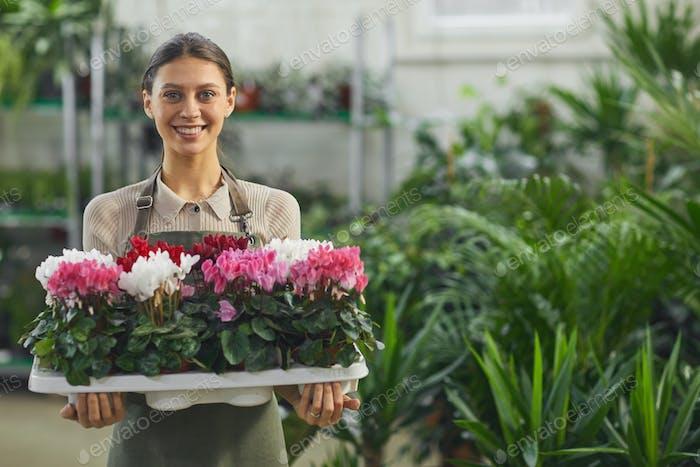 sonriente mujer posando en tienda de flores