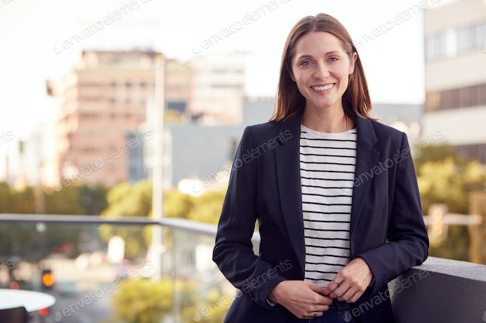 Portrait Of Smiling Businesswoman Standing Outside Office Building With City Skyline In Background