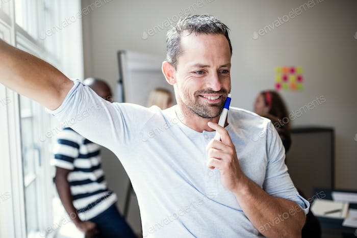 Designer smiling after a whiteboard presentation to office colleagues