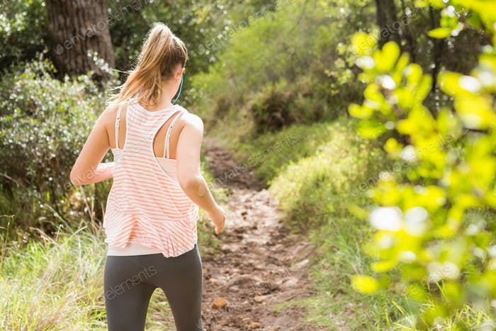 Blonde athlete jogging on trail in the nature