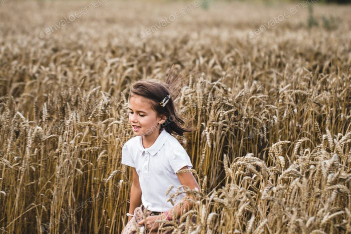 Close up of happy girl with long blonde hair running to the camera through barley field