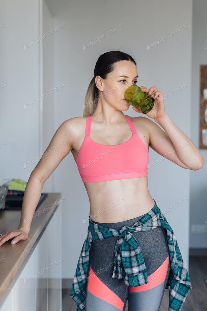 Junge Frau trinken ein Glas Wasser nach dem Training
