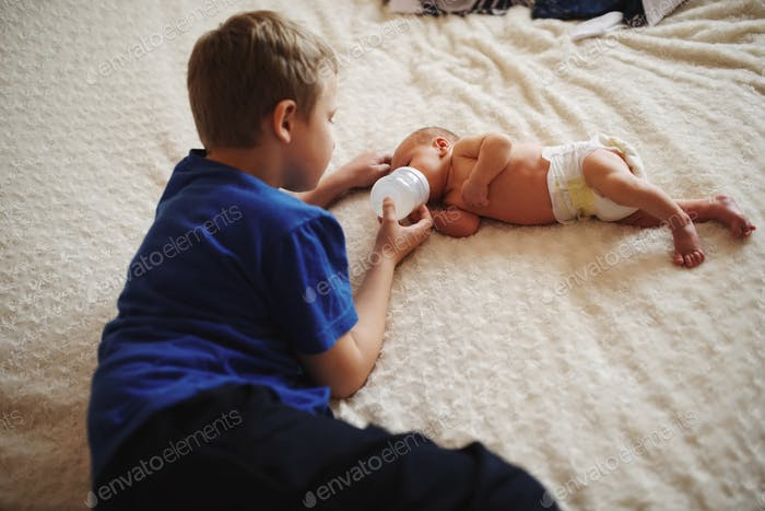 boy feeding newborn baby with bottle of milk