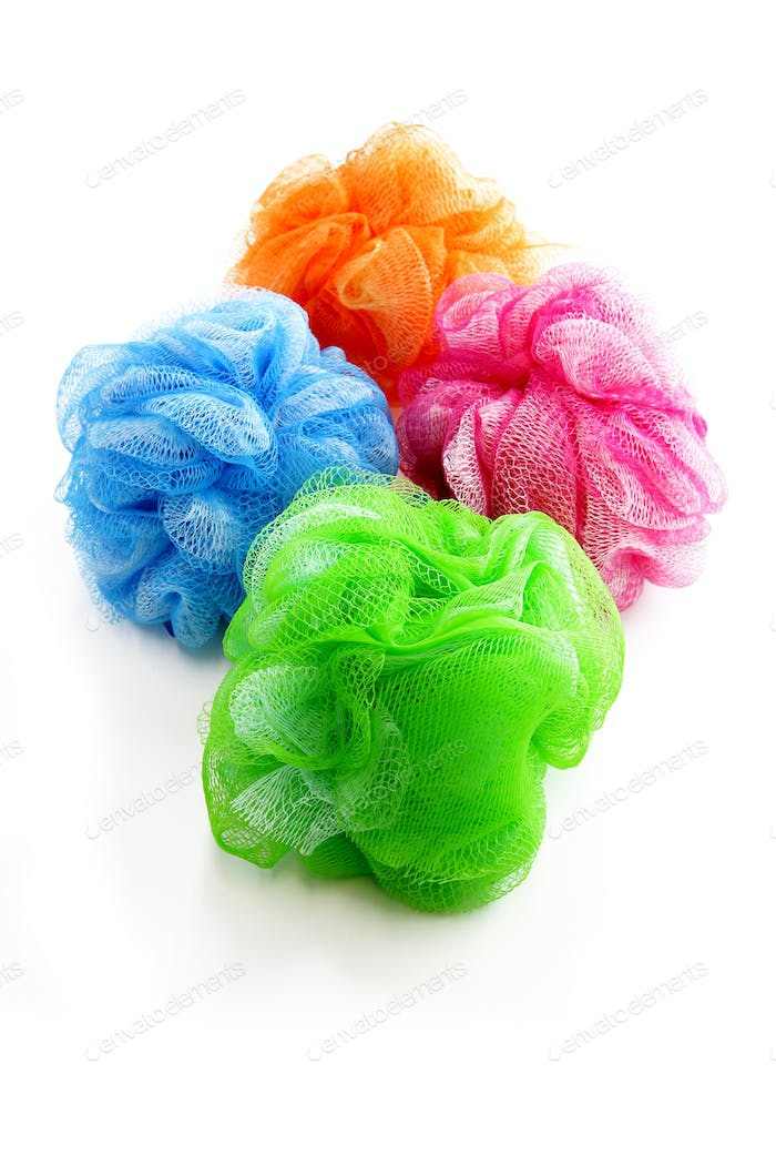 Four colorful shower scrubbers