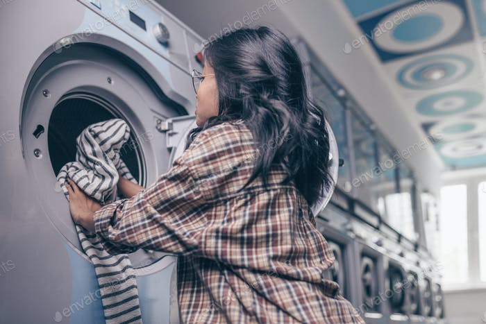 A young girl at a washing machine