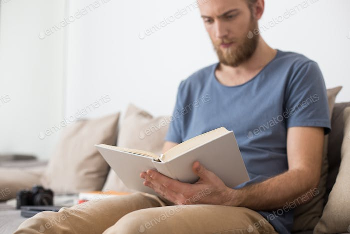 Man sitting on gray sofa and thoughtfully reading book at home