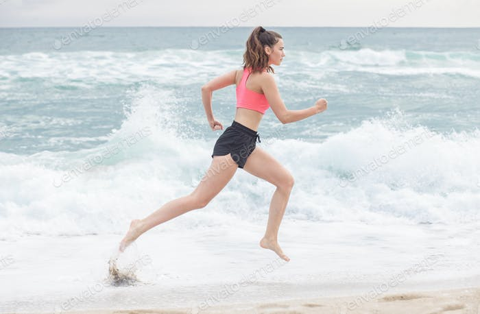 attractive sporty woman running along the beach