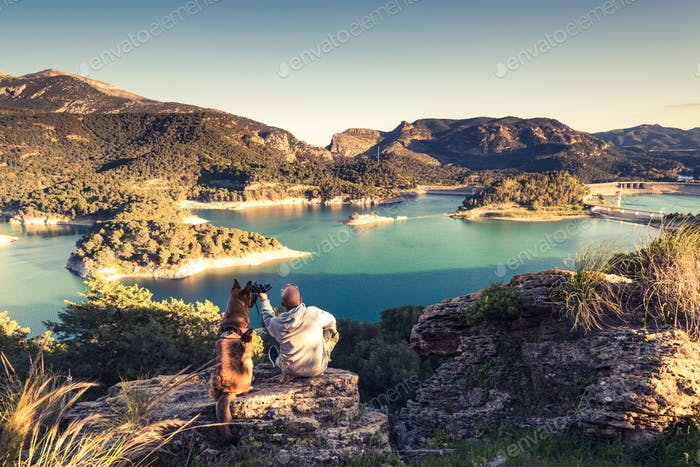 Travellers couple looking at lake from hill