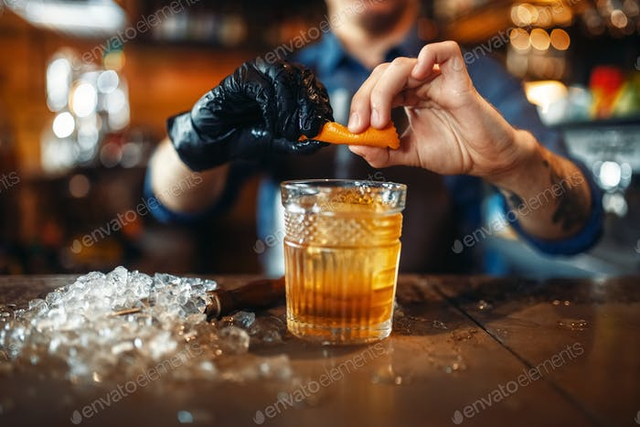 Bartender adds orange skins to alcoholic beverage