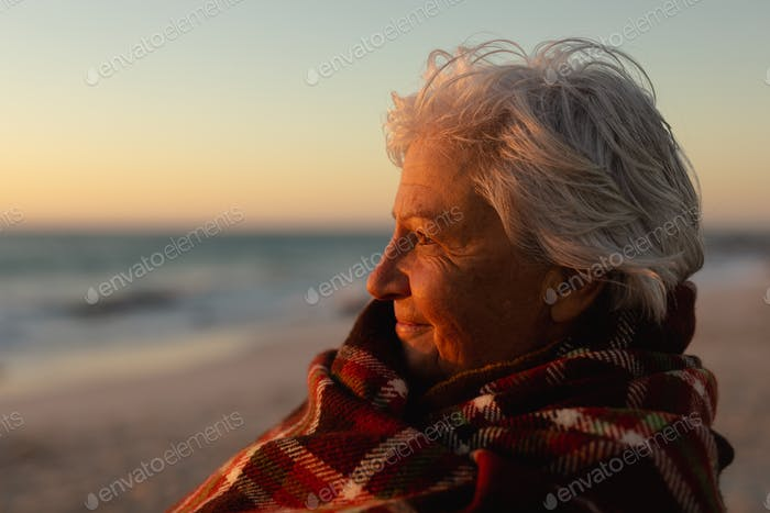 Old woman relaxing at the beach
