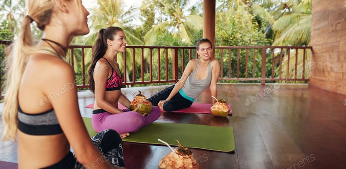 Young women relaxing with coconut juice at yoga class