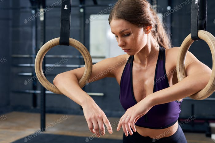 Tired Young Woman Training on Gymnastic Rings