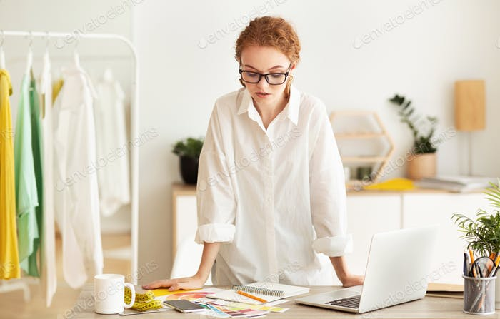 Serious fashion stylist working and standing at desk