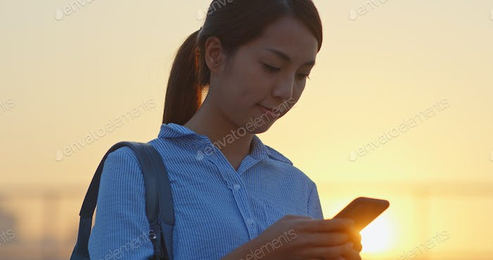 Asian Woman use of cellphone under sunset in Hong Kong