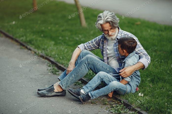 Großvater mit Enkelkind sitzt in einem Sommerpark