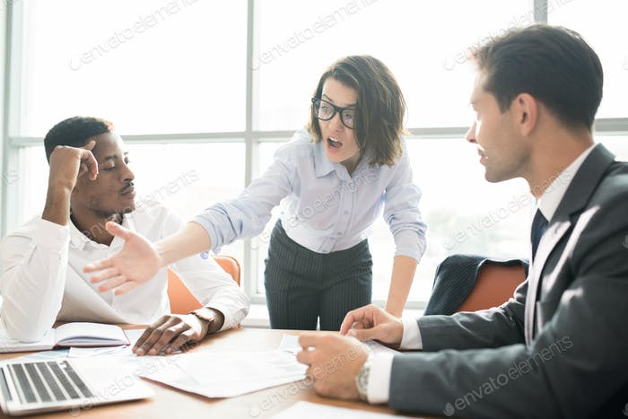 Emotional businesswoman scolding colleagues while checking their