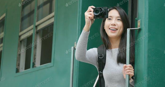 Woman taking photo on digital camera on train