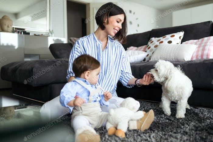 Schöne junge Mutter mit ihrem Baby spielt mit Hund im Wohnzimmer zu Hause.